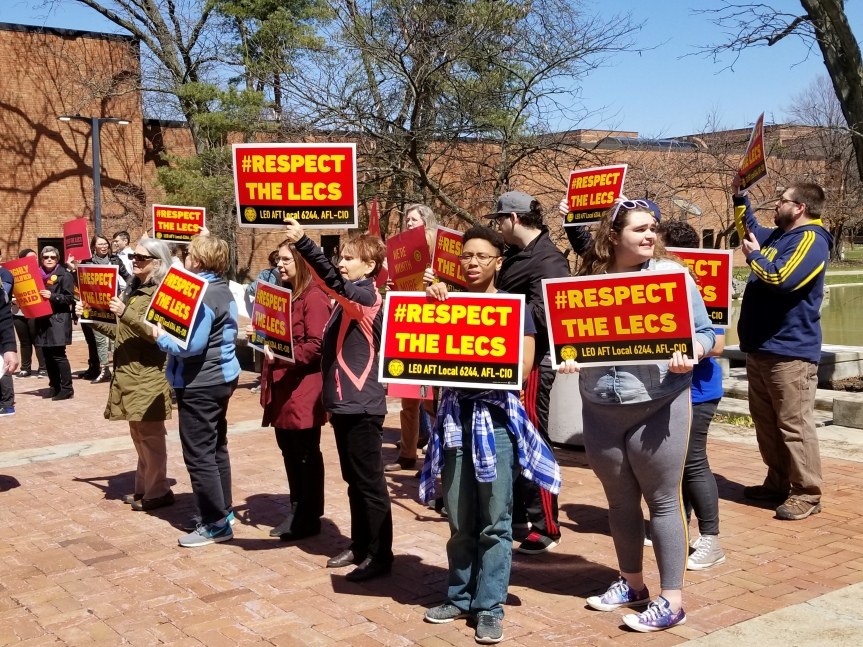 A group of LEO lecs and student allies hold aloft signs that read #Respect The Lecs.